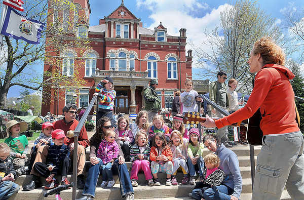 """F. BRIAN FERGUSON/THE REGISTER-HERALD=Maura Kistler, owner of Water Stone Outdoors in Fayetteville, right, plays """"You Are My Sunshine"""" as parents and children sing along on the steps of the Fayetteville Courthouse during Saturday's 8th Annual New River Earth Day Celebration."""