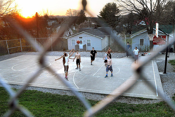 """F. BRIAN FERGUSON/THE REGISTER-HERALD=Oak Hill teens enjoy a game of """"Shirts and Skins"""" on the United Methodist Church Playground on Main Street of Oak Hill on a warm April evening in Oak Hill."""
