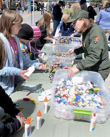F. BRIAN FERGUSON/THE REGISTER-HERALD=Robin Snyder with the National Park Service, right, teaches kids how to make art out of household items of trash during Saturday's 8th Annual New River Earth Day Celebration.