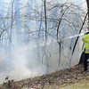 F. BRIAN FERGUSON/THE REGISTER-HERALD=Beckley Firefighters battled flames on a wooded lot behind a home on Dogwood Lane in Maxwell Hill on Wednesday afternoon.