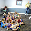 """F. BRIAN FERGUSON/THE REGISTER-HERALD=Mary Jones, right, of Mountain Heart reads """"Pete the Cat"""" to the kids during story time as Mike Stafford, also of Mountain Heart plays a tune."""