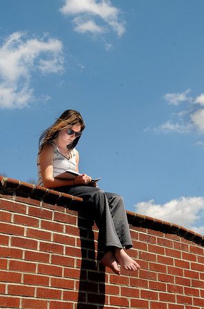 F. BRIAN FERGUSON/THE REGISTER-HERALD=Laura Ward, a Beckley native and a student at Appalachian Bible College, enjoys a geat day to study outside as she takes in Wednesday's sun in front of Hoops Hall on the campus.