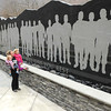 Camelia Flowers, of Whitesville, holds her two children. Allie, left, and Audree Flowers, in front of the miners memorial wall on Main Street in Whitesville.<br /> Rick Barbero/The Register-Herald