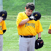 Will Bailey, left, Lance Richmond and Gabriel Turner, ball players for the Pirates at Beckley Little League, put their heads down during the singing of the national anthem for Beckley Little League's opening ceremony.<br /> Rick Barbero/The Register-Herald
