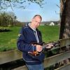 F. BRIAN FERGUSON/THE REGISTER-HERALD=Donnie Ray Mayhew strums on his Mandolin in Oak Hill.
