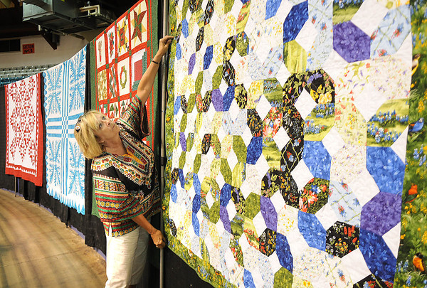 Marsha Smith, co-chair Appalachian Treasures Quilt Show, helps hangs quilts for the Appalachian Arts & Crafts Festival at the Beckley-Raleigh County Convention Center.<br /> Rick Barbero/The Register-Herald