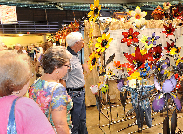 Craft lovers take in a colorful display of hand-made flowers during Friday's Appalachian Arts and Crafts festival at the Raleigh County Convention Center. F. Brian Ferguson. F. Brian Ferguson