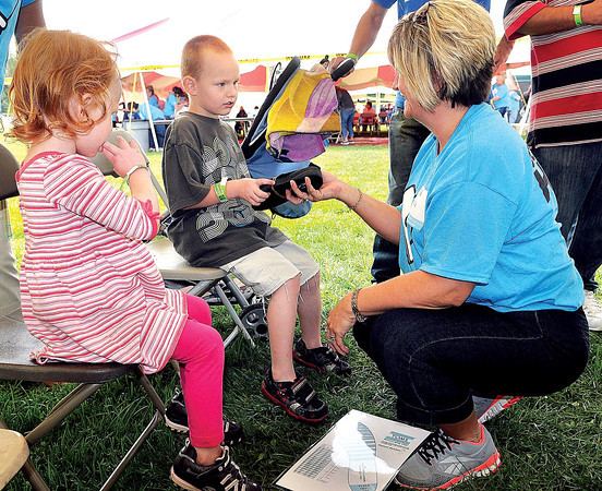 Hallie Marie Bess, 3, left, and older brother Frank Bess, 5, center, both of Beckley, get fitted for free shoes from volunteer Ella Cox, right, during Saturday's Day of Hope event at the YMCA Soccer Complex. F. Brian Ferguson/The Register-Herald