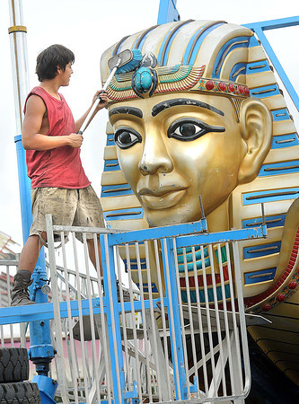 Cesar Sanchez cleans the Pharaoh's Fury ride that's set up for the State Fair in Fairlea. The fair opens this Friday.<br /> Rick Barbero/The Register-Herald