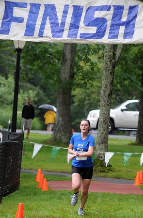 Erica Morgan of Princeton crosses the finish line on a wet Saturday duringthe Triathlon at the Resort at Glade. F. Brian Ferguson/The Register-Herald