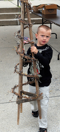 Broc Johnson, 4, of Mullins helps his mother carry out a Christmas Tree craft during Friday's Appalachian Arts and Crafts festival at the Raleigh County Convention Center. F. Brian Ferguson