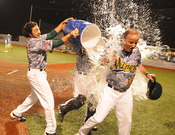 James Woods, left, and Josh Galvan, pour water on head coach Tim Epling after winning the championship game against Quincy Gems.<br /> Rick Barbero/The Register-Herald
