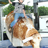 Clay Aliff, 7, of Beckley, son of Kenny and Andrea Aliff, of Beckley, rides a mechanical bull during opening day for the West Virginia State in Fairlea.<br /> Rick Barbero/The Register-herald