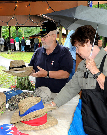 James Lilly, left, and wife Betty Lilly, right, of Front Royal, Va check out some Lilly hats. during Saturday's Lilly Family Reunion. F. Brian Ferguson/The Register-Herald