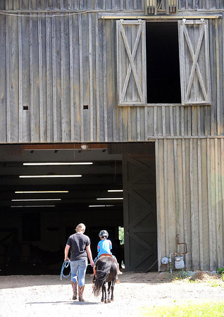 Amanda Griffith, of Odd, left, wlaks her student on a pony, back to the stable at the Equestrian Center at The Resort at Glade Springs.<br /> Rick Barbero/The Register-Herald