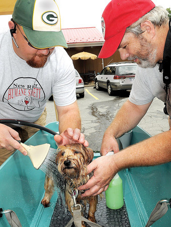 "Red McKinney, left, and David King, right, both with the New River Humane Society, give ""Lexi"" a bath at Diogis in Fayetteville during Saturday's dog wash.. F. Brian Ferguson/The Register-Herald"