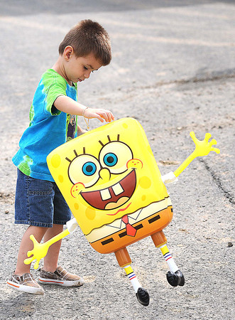 Tanner Jones, 3, son of Marty and Tina Jones, of Princeton, walks with his spongebob balloon during opening day for the West Virginia State in Fairlea.<br /> Rick Barbero/The Register-herald