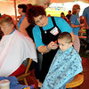 Earl Bennett, 3, of Pax gets a back-to-school haircut from Brenda Edwards during Saturday's Day of Hope event at the YMCA Soccer Complex. F. Brian Ferguson/The Register-Herald