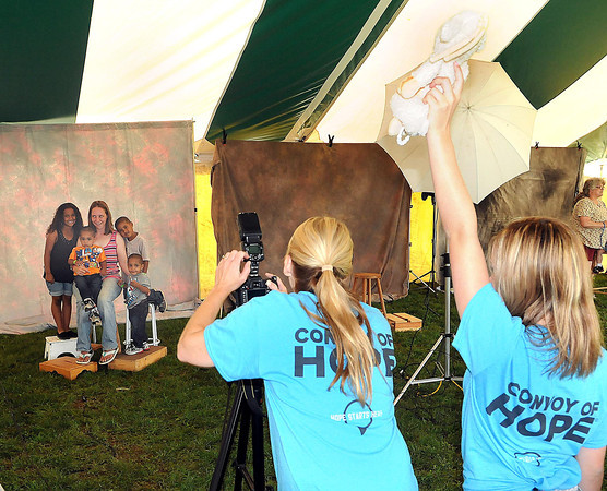 Photographer Stephanie Todd, center, and daughter Maddie Todd give free family portraits during Saturday's Day of Hope event at the YMCA Soccer Complex. F. Brian Ferguson/The Register-Herald