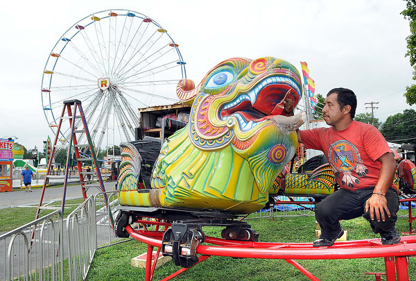 Eugenio Meadoza does some painting touch up work on the Ren Express ride on the State Fair grounds in Fairlea getting ready for the State Fair that starts Friday.<br /> Rick Barbero/The Register-Herald