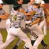 Griffin Moore, of WV Miners, gets mobbed by teammates after getting the winning hit against the Quincy Gems in the championship game.<br /> Rick Barbero/The Register-Herald