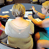 Mary Ann Foster, right, teaches Shannon McDaniel, center, and her daughter, Mackenzie McDaniel, left, both of Beckley, how to use an I Pad at Tamarack on Saturday. F. Brian Ferguson/The Register-Herald