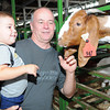 Mike Haynes, of South Charleston, holds his grandson Robert Dawson, 2, while petting a goat during opening day for the West Virginia State in Fairlea.<br /> Rick Barbero/The Register-herald