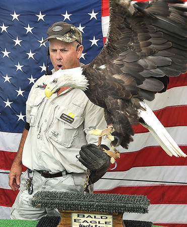 Johnathan Wood, owner of Extreme Raptors, holds up a bald eagle during his show at the West Virginia State in Fairlea.<br /> Rick Barbero/The Register-herald