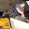 Jonathan Holsten works on a cub cadet at his new business location on Central Ave in Beckley.<br /> Chris Hancock/The Register-Herald