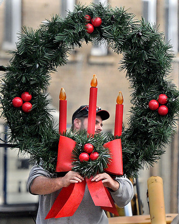 Bow Tie=Mt. Hope City worker Bobby Dillon puts the finishing touches on one of the town's Christmas decorations that he was helping hang along Main Street this week. F. Brian Ferguson/The Register-Herald