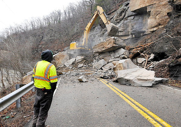 Gilbert Spence, a contractor with Vecellio & Grogan Inc., looks on as an excavator continues the cleanup effort at the site of the Coal River Road rock slide Monday afternoon.<br /> Brad Davis/The Register-Herald