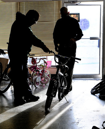 Chief Organizer, Arnold Bolen, left, of Boy Scout Troop 103 and volunteer Walter Winant, right, begin Saturday morning wheeling in the donated bikes at the Beckley/Raleigh County Convention Center. Bolen is on his 15th year of collecting and repairing donated bikes for the Mac Toy Fund.  F. Brian Ferguson/The Register-Herald