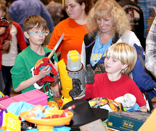 C.J. Overbay (right), 8, finds the perfect toy as his cousin McClaren Conner, 10, follows close behind with an armful of toys while Overbay's mother, Christy, looks on during Mac's Toy Party Saturday morning at the Beckley-Raleigh County Convention Center.<br /> Brad Davis/The Register-Herald
