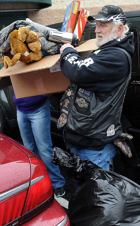 "Brother's of the Wheel member ""Tourch"" and his fellow club members joined in with volunteers to carry toys to cars on Sunday during the Wyoming County Toy Fund at Wyoming East High School. F. Brian Ferguson/The Register-Herald"
