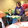 Laci Poland, 7, second from left and her mother Heather Poland, volunteers for the United Methodist Temple's 18th annual community church dinner, serve meals to Grover, left and Dewayne Holshouser, of Coal City. The dinner was helfd from 11 a.m. to 2 p.m. at the Place, directly behind the church.<br /> Rick Barbero/The Register-Herald