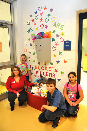 Teresa Kelly, left, information referral specialist, United Way, left, receives food donated by Beckley Elementary students. Picture with Kelly from left, Taylor McDaniel, Madison Williams and Jay Meadows.<br /> Rick Barbero/The Register-Herald
