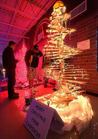 Visitors check out some of the unique Christmas tree designs on display during the 13th annual Festival of Trees at the Academy of Careers and Technology Tuesday night. At front is a tree designed by carpentry students, while the red tree in the background was designed by welding students.<br /> Brad Davis/The Register-Herald