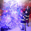 Beckley residents (front to back) Alex, 2, and Alden Fitzpatrick, 3, marvel at a glowing, fog-emitting Christmas tree built by electrical technology students as their Aunt, Sandra Graham (back) looks on during the 13th annual Festival of Trees at the Academy of Careers and Technology Tuesday night.<br /> Brad Davis/The Register-Herald