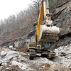 An excavator moves into position to continue the cleanup at the site of the Coal River Road rock slide Monday afternoon.<br /> Brad Davis/The Register-Herald