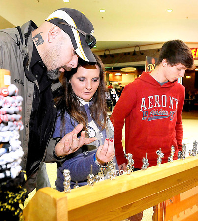 Oak Hill residents Alisha Harrah and her boyfriend Lee Epperly take a look at some merchandise available at the Heavenly Charms kiosk while Harrah's son, Joseph (right), searches for a last minute Christmas gift for his girlfriend Tuesday afternoon at the Crossroads Mall. Many last minute shoppers across the area were scrambling on Christmas Eve to complete their lists, while some were just getting started.<br /> Brad Davis/The Register-Herald