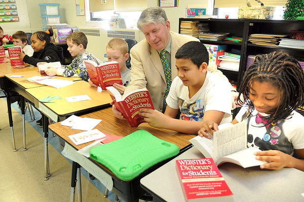Larry Ford, vice president Raleigh County Board of Education, 5th from left, looks over dictionary's with third graders he handed out at Stratton Elementary School. Pictured with Ford from left, Chris Madden, Sanae Johnson, Isaiah Reed, Nathan Shrewsberry, Darren Johnson and Janique Shaw. 1000 dictionary's were donated by the Rotary Club and presented to all the third graders in Raleigh County.<br /> Rick Barbero/Ther Register-Herald