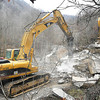 An excavator equipped with a giant jackhammer breaks apart some of the remaining larger portions of last weekend's rock slide Monday afternoon.