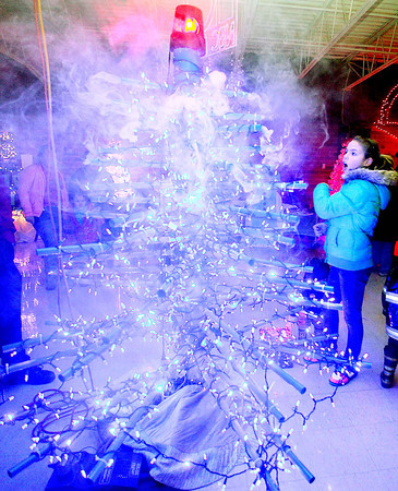 Destiny Blankenship, 11, watches in amazement as a Christmas tree designed by electrical technology students begins to emit fog during the 13th annual Festival of Trees at the Academy of Careers and Technology Tuesday night.<br /> Brad Davis/The Register-Herald