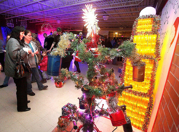 Robin Burgess, far left, and Sonnia Whiasman check out some of the unique Christmas trees on display during the 13th annual Festival of Trees at the Academy of Careers and Technology Tuesday night.<br /> Brad Davis/The Register-Herald