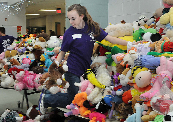 Volunteer Myleigh Stewart climbed the mountain of stuffed animals looking for just the right one on Sunday during the Wyoming County Toy Fund at Wyoming East High School. F. Brian Ferguson/The Register-Herald