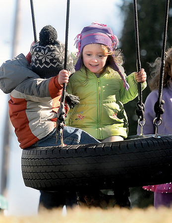 Tyson Stovall, 2, left, and Ava Mullins, 3, right, take in Friday's sun as they enjoy a ride on their tire swing, outside their Grandview home. F. Brian Ferguson/The Register-Herald