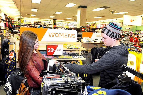 Oak Hill residents Abigail Forren and Jason Young shop for a gift for Young's sister Tuesday afternoon at Hibbett Sports in the Crossroads Mall. Many last minute shoppers across the area were scrambling on Christmas Eve to complete their lists, while some were just getting started.<br /> Brad Davis/The Register-Herald