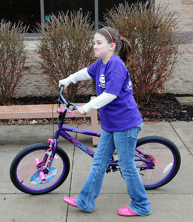 Volunteer Lexi Bowen, 10, wheeled out a bike on Sunday during the Wyoming County Toy Fund at Wyoming East High School. F. Brian Ferguson/The Register-Herald