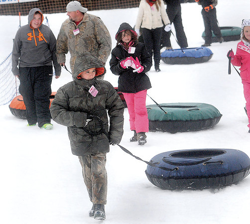 Zacheri Hannamah, 10, foreground, joined his stepbrother Kenan Jessup, 12, left, stepfather Kenny Jessup, and sister, Lasone Hannamah, 9, for some snow tubing during the Volunteer Youth Department year-end party on Monday at Winterplace. F. Brian Ferguson/The Register-Herald