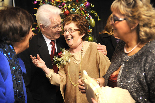 Sherry Rose, third from left, gets greeted by Ginger and Lonnie Cole, of Beckley left, and Lisa Barton, of Beckley, right, during the YMCA of Southern West Virginia Spirit of Beckley Community Service Award Banquet.<br /> Rick Barbero/The Register-Herald